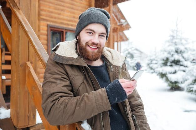 Giovane barbuto allegro che utilizza smartphone all'aperto in inverno