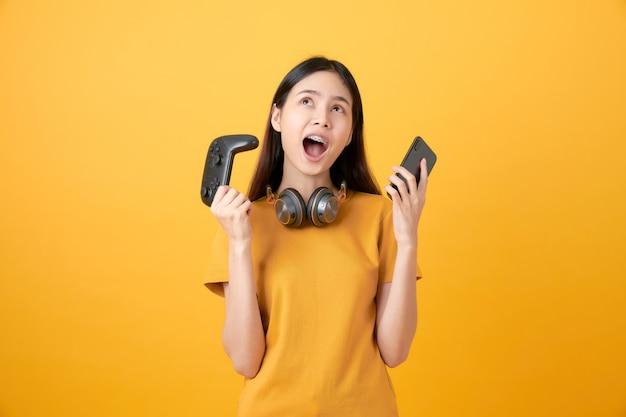 Bella donna asiatica allegra in maglietta gialla casuale e giocare ai videogiochi facendo uso delle leve di comando con le cuffie e lo smartphone