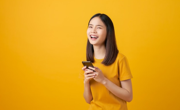 Bella donna asiatica allegra che tiene smartphone su sfondo giallo chiaro.