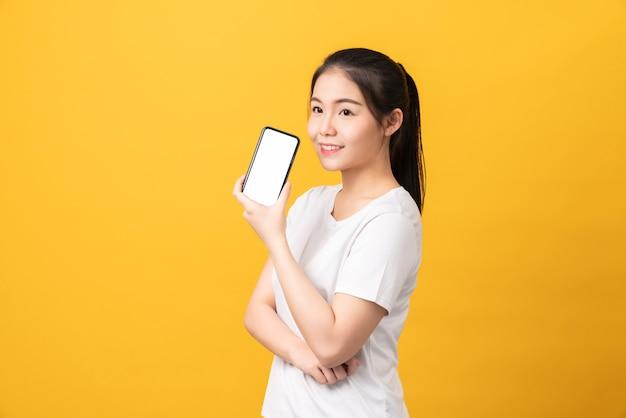 Bella donna asiatica allegra che tiene smartphone e messaggio di battitura a macchina su fondo giallo chiaro.