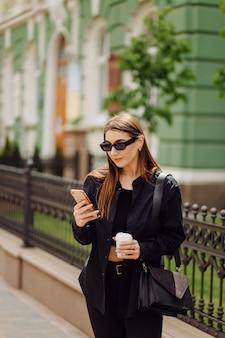 La bella donna castana allegra di buon umore usa il telefono esterno
