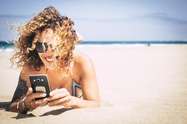 Allegra bella caucasica middlea ge giovane donna sorridi e usa il telefono cellulare in spiaggia per connetterti con amici e genitori bianco goditi una vacanza in un resort di isole tropicali