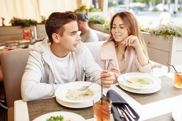 Una coppia allegra e bella si rilassa su una terrazza estiva in un ristorante con cibi e bevande. il ragazzo e la ragazza si divertono sulla terrazza