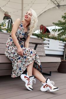 Allegra bella ragazza divertente con labbra rosse in un vestito alla moda con un motivo con eleganti scarpe da ginnastica si siede su una panca di legno e si gode il momento in città