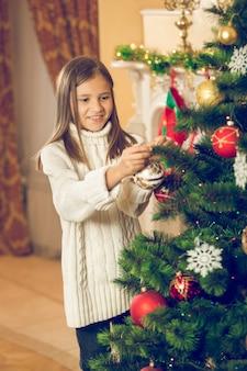 Bella ragazza allegra che decora l'albero di natale con le palline