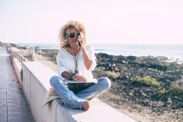 Allegra bella donna caucasica di mezza età con i capelli ricci sorridere e parlare al telefono cellulare sedersi vicino all'oceano in attività all'aperto tecnologica. yoga gambe incrociate e laptop per persone moderne