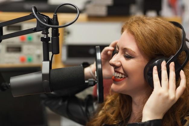 Bello cantante allegro che registra una canzone