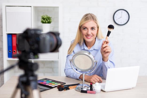 Video blogger allegra e bella donna che registra video vlog su trucco e cosmetici