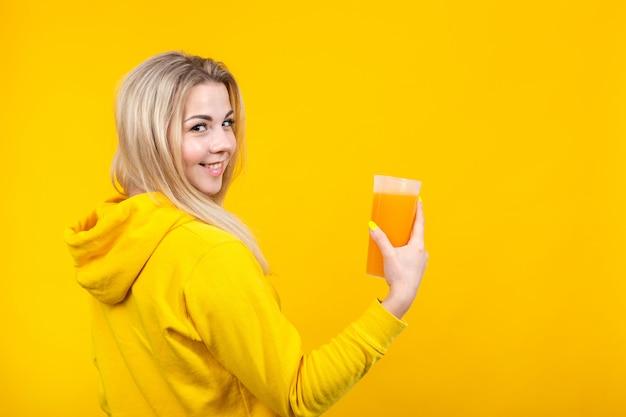 Bella giovane donna bionda allegra in vestiti sportivi casuali gialli che tengono il vetro del succo d'arancia