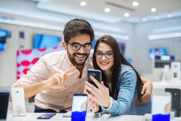 Belle giovani coppie allegre nel grande deposito elettronico luminoso che collauda nuovo telefono. fare shopping insieme e divertirsi.