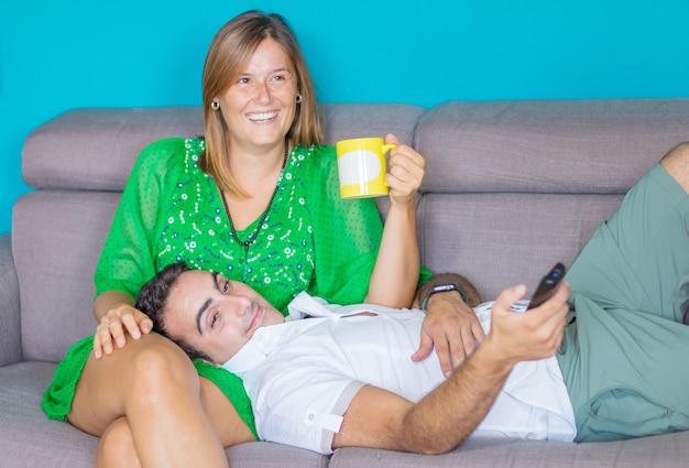 Bella giovane coppia allegra che beve caffè e guarda la tv a casa