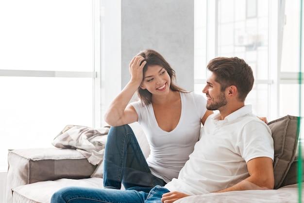 Bella giovane coppia allegra che si siede e che parla sul sofà a casa