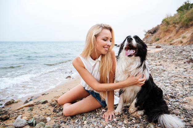Bella giovane donna allegra che abbraccia il suo cane sulla spiaggia