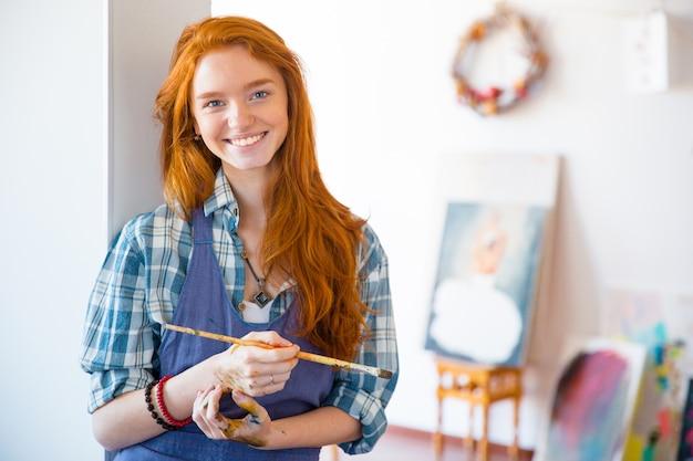 Bella giovane donna allegra pittrice con lunghi capelli rossi che tiene in mano una spazzola e sta in piedi in uno studio d'arte
