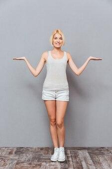 Bella giovane donna allegra che sta e che tiene copyspace su entrambi i palmi sopra il muro grigio