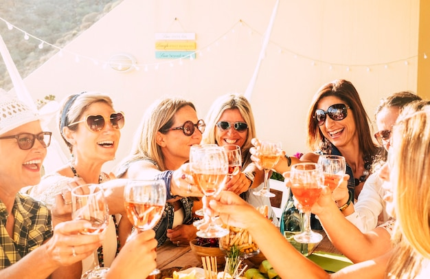 Belle giovani donne allegre che tostano vino insieme, festeggiano e si divertono