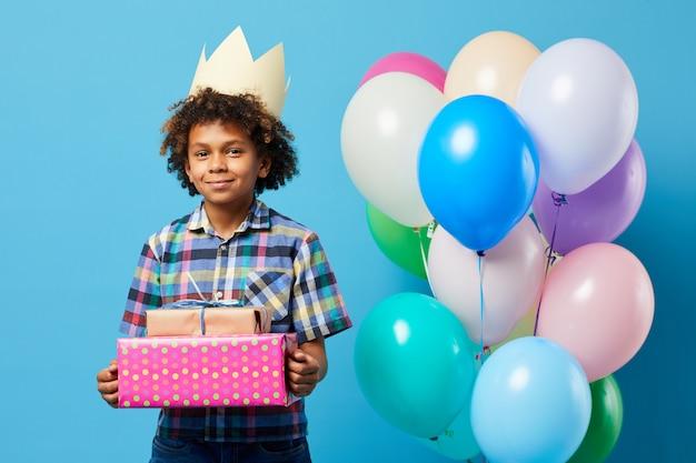 Ragazzo allegro di compleanno che posa sul blu