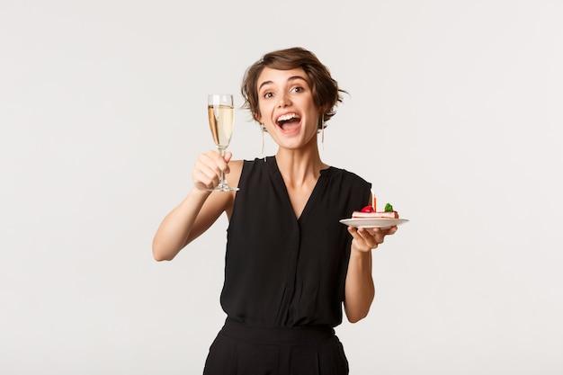 Ragazza allegra di compleanno che celebra, tenendo un bicchiere di champagne e una fetta di torta con la candela accesa, in piedi sopra il bianco.