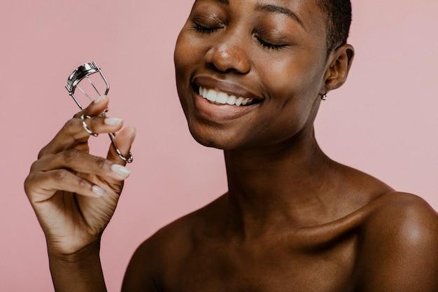 Allegra bellezza femminile nera che usa un piegaciglia
