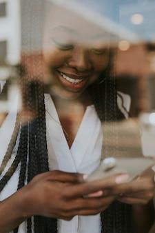 Donna di colore allegra che scrive sul suo telefono