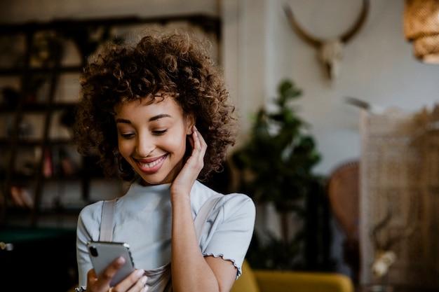 Donna di colore allegra che usa il suo telefono in soggiorno