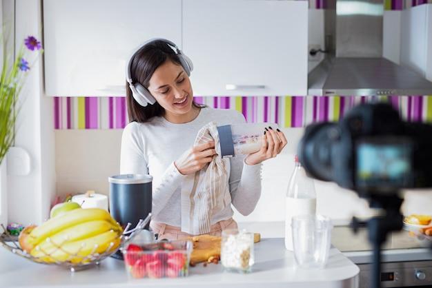 Donna allegra di blogger con la cuffia avricolare sulla testa che si prepara una prima colazione sana. riprese questo processo con la fotocamera.