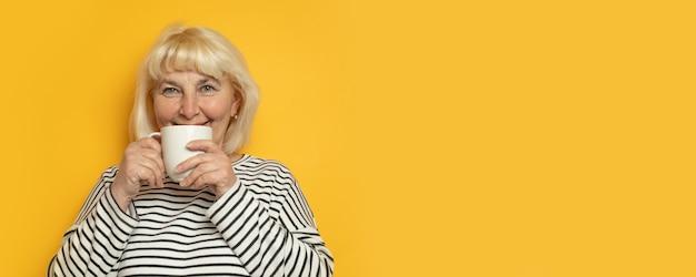 Una donna caucasica bionda allegra di 40 anni che beve tè o caffè caldo su sfondo giallo con uno spazio di copia