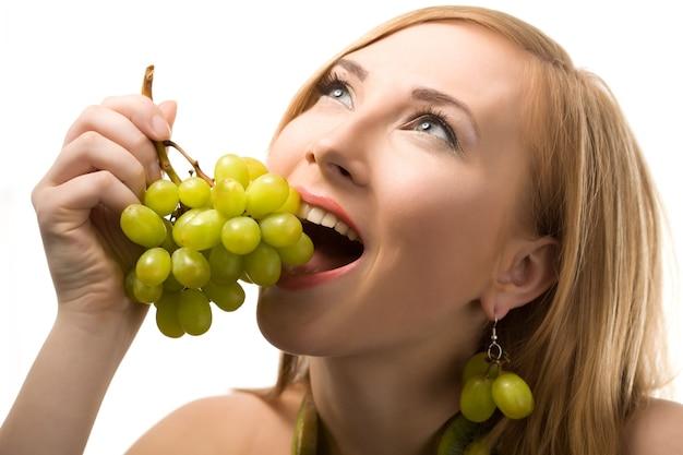 Allegra donna bionda con i capelli corti in posa con uva matura verde nelle mani