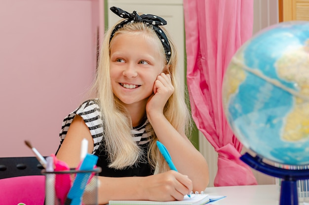 Lookig biondo allegro della ragazza da parte e sorridere. ritorno a scuola e apprendimento a casa