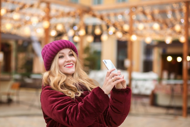 Donna bionda allegra che prende selfie sul telefono cellulare sullo sfondo delle luci di natale