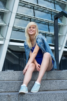 Allegra donna bionda che indossa una giacca di jeans seduta sulle scale della strada