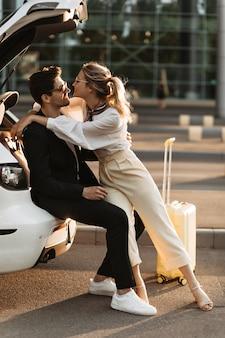 Donna bionda allegra in camicetta bianca, pantaloni beige abbraccia il fidanzato in abito nero