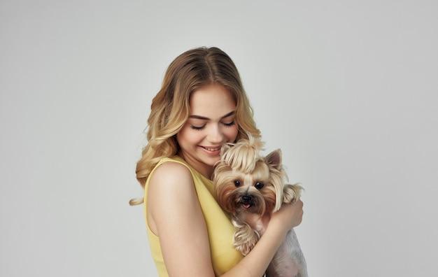 Una bionda allegra in un vestito giallo tiene in mano un cane di razza.