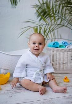La bambina allegra dagli occhi azzurri in accappatoio è seduta sul pavimento vicino al bagno. igiene dei bambini