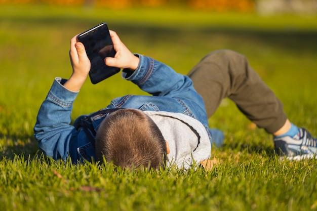 Un ragazzo allegro in una giacca di jeans giace su una panchina e gioca con uno smartphone in un parco cittadino