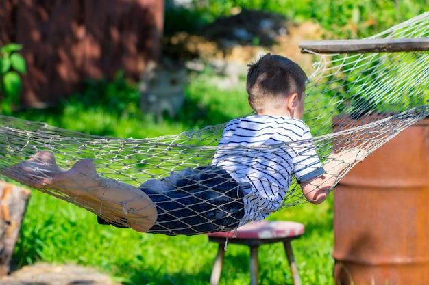 Ragazzo allegro sdraiato su un'amaca in giardino.