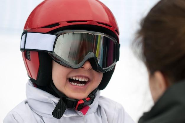 Ragazzo allegro in casco rosso, occhiali da sci e giacca bianca che sorride a sua madre. sport invernali, giovane sciatore, sfondo innevato