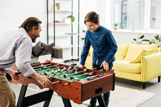 Ragazzo allegro che si rilassa con suo padre in soggiorno e sembra interessato mentre gioca a calcio balilla con lui