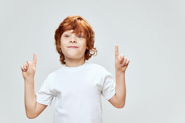 Il ragazzo allegro mostra due mani in su con la maglietta bianca delle dita di indice