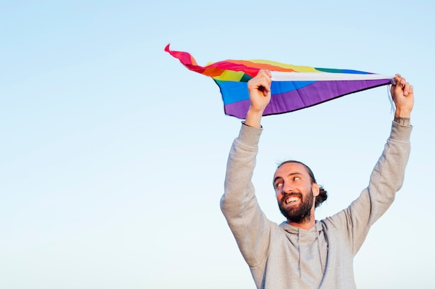 Ragazzo allegro con una bandiera arcobaleno lgbtq sulla spiaggia. giovane che tiene una bandiera arcobaleno contro il cielo blu