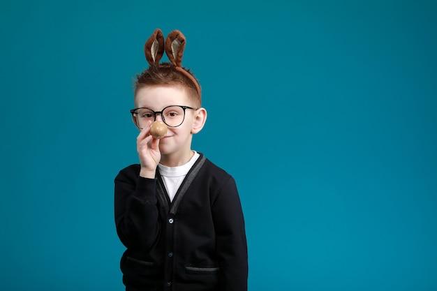Ragazzo allegro con orecchie da coniglio in testa su sfondo blu studio