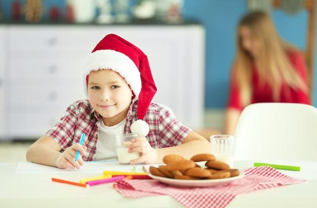 Ragazzo allegro che scrive una lettera a babbo natale, primo piano