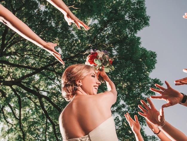 La sposa allegra lancia un bouquet da sposa ai suoi amici. feste e tradizioni