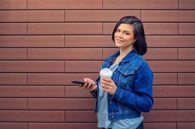 Ragazza caucasica castana allegra in una giacca di jeans blu con lo smartphone in piedi davanti al muro di mattoni che tiene in mano il caffè caldo.