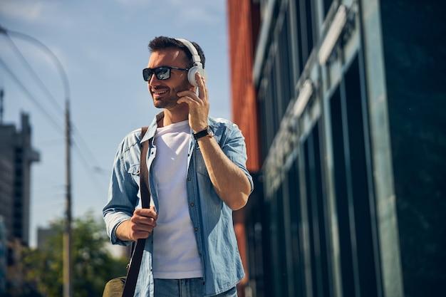 Persona di sesso maschile bruna allegra che indossa le cuffie mentre ascolta la sua musica preferita durante la passeggiata