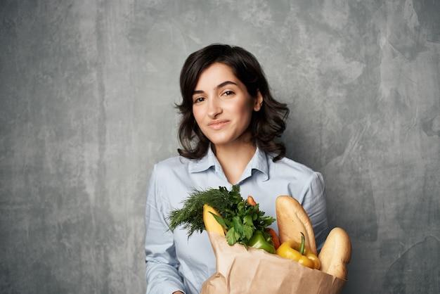 Bruna allegra con un pacchetto di consegna della spesa di generi alimentari. foto di alta qualità
