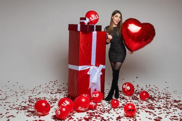 Donna castana allegra in vestito e stivali che tengono palloncino a forma di cuore rosso