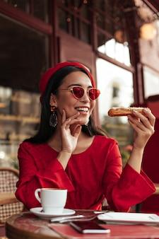 La donna castana allegra in vestito rosso, berretto luminoso e occhiali da sole colorati alla moda sorride, si siede al bar con una tazza di caffè e tiene un delizioso eclair