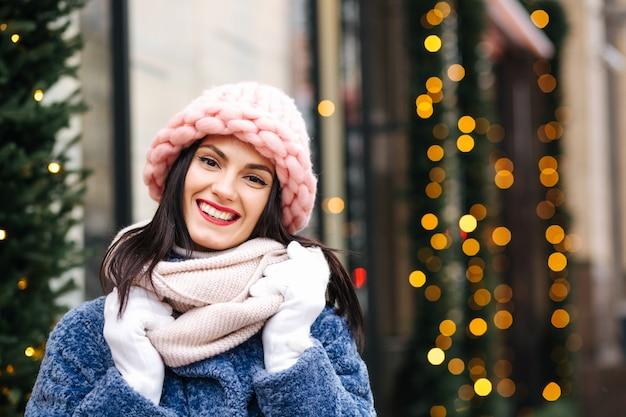 La donna castana allegra indossa un berretto rosa chiaro lavorato a maglia e una sciarpa che cammina in città decorata con ghirlande. spazio per il testo