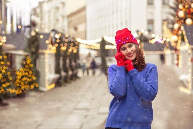 La donna castana allegra indossa il berretto rosso e il maglione blu che camminano alla fiera di natale nella piazza centrale della città. spazio per il testo